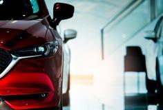 汽车前红色视图 新的豪华小型客车在现代陈列室里停放了待售 售车行办公室 汽车零售店 免版税库存照片