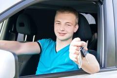 汽车司机 显示汽车钥匙的白种人青少年的男孩在新的汽车 免版税库存照片
