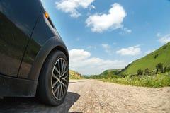 汽车和一辆手纺车的边的特写镜头沿沥青高速乘坐 免版税库存图片