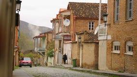 汽车和公民在狭窄的大卵石街道上有舒适房子的在英王乔治一世至三世时期村庄 影视素材
