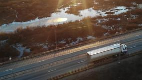 汽车和用物品装载的半货物卡车驾驶沿一条空的高速公路