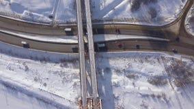 汽车和继续前进冬天高速公路的货物卡车在火车桥梁寄生虫视图下 在雪道的汽车通行在冬天 股票视频