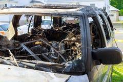 汽车和轮子的前面翼没有轮胎在火以后 被烧的汽车 库存照片