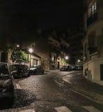 汽车在一条安静的鹅卵石街道上停放了在蒙马特,巴黎,法国的晚上 库存照片