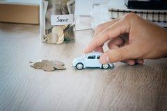 汽车在书桌上的人手上有在瓶子银行挽救概念的blured金钱硬币的维修费用和税汽车的,温暖的口气 免版税库存照片