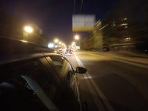 汽车在夜路高速移动在城市 免版税图库摄影