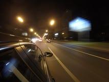汽车在夜路高速移动在城市 免版税库存照片