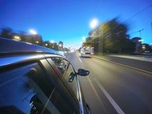 汽车在夜路高速移动在城市 库存图片