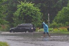 汽车在大雨中乘坐在一条被充斥的路 库存图片