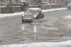 黑汽车在大水坑乘坐在多雪的天 在曼彻斯特的路的雨夹雪飞溅 03/03/2016曼彻斯特,英国editoria 库存图片