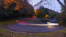 汽车在曲线点燃在晚上在城市 库存图片