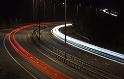 汽车在机动车路的光足迹在晚上 免版税库存图片