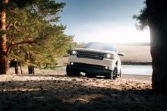 汽车在沙子的陆虎路华汽车立场在湖和森林附近白天的 免版税库存照片