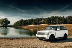汽车在沙子的陆虎路华汽车立场在湖和森林附近白天的 免版税库存图片