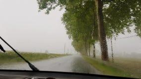 汽车在路在倾吐的雨中移动 股票录像