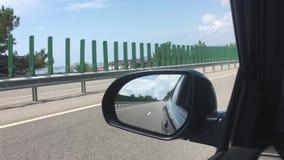 汽车在路,旁边后视镜的看法,在镜子的反射乘坐 海湾的看法从汽车的 关闭 影视素材
