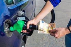 给汽车坦克加油和拿着欧洲金钱的妇女 免版税图库摄影