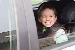 汽车安全位子的愉快的小男孩 免版税库存图片