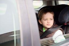 汽车安全位子的担心的小男孩 免版税图库摄影