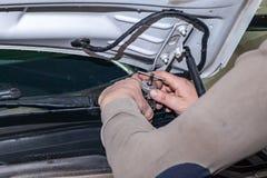 汽车安装工松开零件有一把板钳的风档刮水器有在机舱的绿色把柄的在车修理 图库摄影