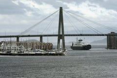 汽车客船在港口进入斯塔万格港口,斯塔万格,挪威的吊桥下 免版税库存照片