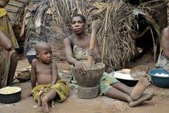 汽车密林  闹事 2008个第2个非洲非洲baka中央女孩密林11月共和国部落白人妇女 鲍卡妇女烹调食物,击碎在灰浆的面粉 库存照片
