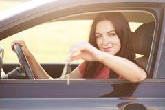 汽车所有者把握关键,坐在驾驶席,保留在轮子的手,给或者卖汽车做广告 美丽的深色的妇女驾驶ve 免版税库存图片
