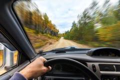 汽车推进低谷由土路的秋天森林 免版税库存照片