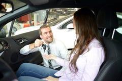 汽车推销员在售车行中移交汽车钥匙给cus 库存图片