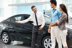 汽车推销员在陈列室邀请顾客 免版税库存照片