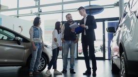 汽车推销员显示关于他们新的汽车的年轻家庭信息 免版税库存照片