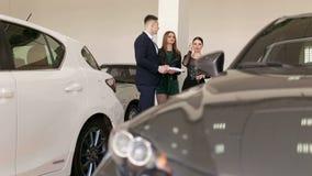 汽车推销员谈话与两个女孩在陈列室里 买一辆新的汽车 股票录像