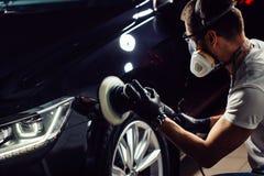 汽车擦亮剂蜡 拿着磨光器的工作者手 免版税库存照片