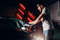 汽车擦亮剂蜡 拿着磨光器的工作者手 免版税库存图片