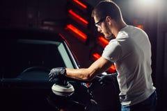 汽车擦亮剂蜡 拿着磨光器的工作者手 图库摄影