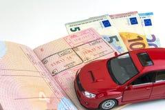 汽车旅行的概念:与边界邮票的护照 一些票据欧元现金 红色汽车模型 在空白背景 免版税库存图片