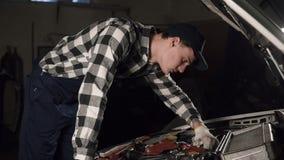 汽车服务、修理、维护和人概念-技工人佩带的工作长袍和盖帽有手套的在他的手上 股票视频