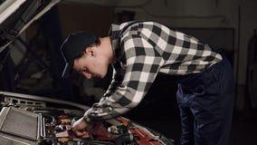 汽车服务、修理、维护和人概念-运转在车间的技工人佩带的工作长袍和盖帽 股票视频