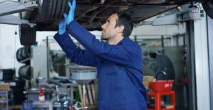 汽车服务的专家汽车机械师,修理汽车,做传输和轮子 概念:机器,缺点二修理  免版税库存照片