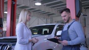 汽车服务,客户女性移交车钥匙给修理的汽车机械师并且握手在背景机器的在 股票录像