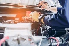 汽车机械师使用一个多用电表电压表检查电压l 免版税库存图片