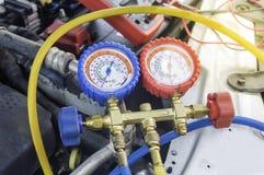 汽车机械师使用在空气压缩机,液体的一个压力表 免版税库存照片