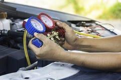 汽车机械师使用在空气压缩机,液体的一个压力表 免版税图库摄影