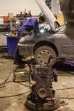 汽车机械师修理在车库的一辆汽车 免版税库存照片