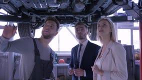 汽车机械师在站立在汽车下的手上劝告顾客年轻夫妇和举行剪贴板上升在推力 股票视频