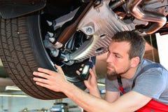 汽车机械师在车间修理车 免版税库存照片