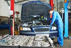 汽车机械师安装工在工作 免版税库存图片