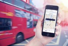 汽车查寻在苹果计算机iPhone屏幕上在女性手上被显示的Uber app 免版税库存照片