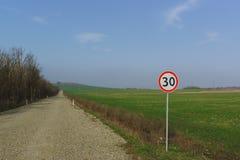 汽车标志限速30公里每个小时是在沿绿色射击的领域的土路一边 免版税库存照片