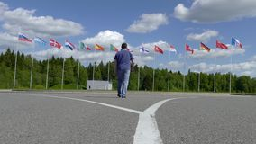 汽车横渡去有旗子的旗杆的一个人的道路 股票视频